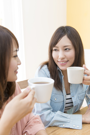 2 women to each other staring while drinking coffee