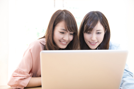 family and friends: Two women touch notebook PC