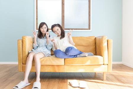 2 人の女性がソファに座る 写真素材