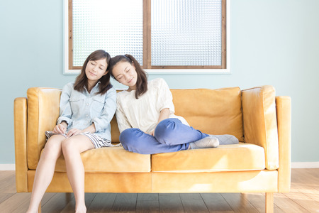 Two women sit on the sofa