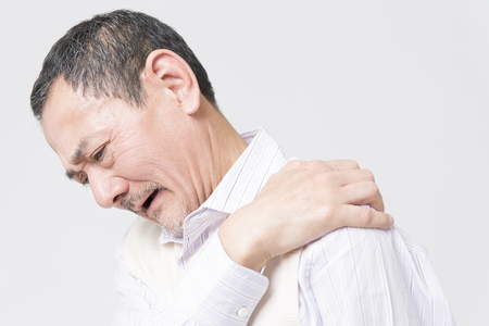 stiffness: Senior male complaining of shoulder stiffness Stock Photo