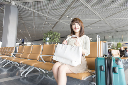 Women smile sitting in the waiting area of the airport Stock Photo