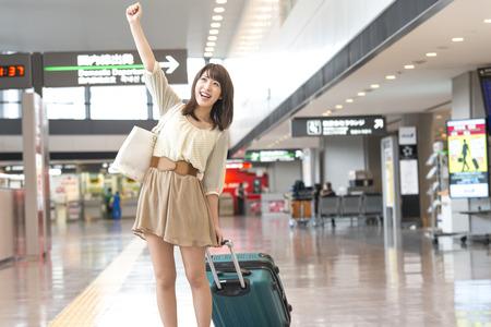 空港でガッツポーズする女性