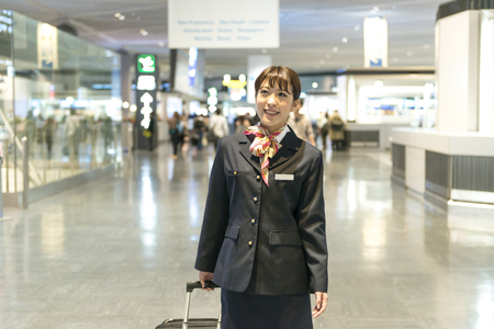 Flight attendant walking with carry case