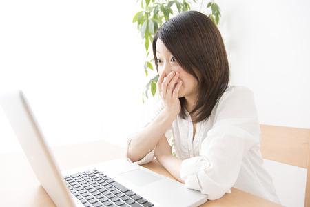 女性は驚いて見ているノート パソコン 写真素材