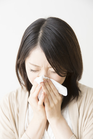 blowing nose: Woman blowing nose