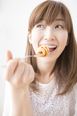 early thirties: Woman eating pasta