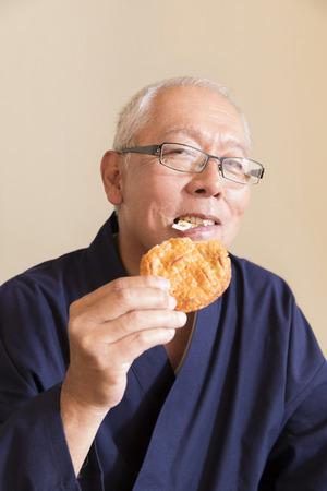 Senior men eating rice crackers