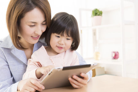 Mother with girl to work with Tablet PC Stock Photo