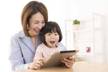 Mother with girl to work with Tablet PC 스톡 콘텐츠
