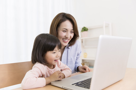 Mother with girl to work with PC photo