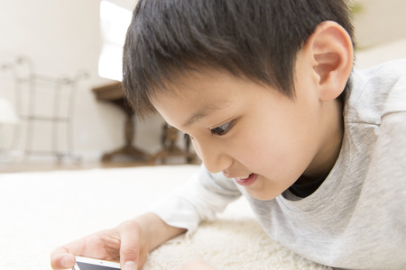 one room school house: Boy playing with smartphone Stock Photo