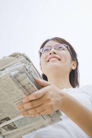 bundled: women with the bundled newspaper Stock Photo