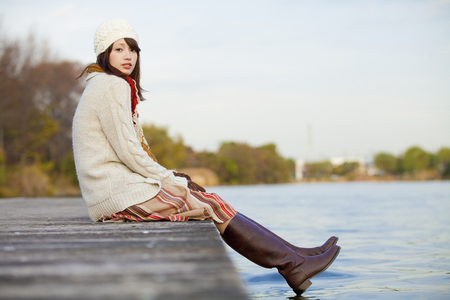 far away look: Woman smiling sitting on the riverside