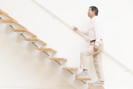 年配の男性が階段を登る