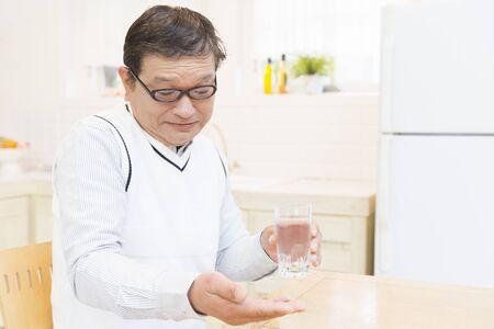 the elderly residence: Senior men drinking medicine Stock Photo