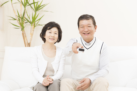 the elderly residence: Senior couple to operate the remote control Stock Photo