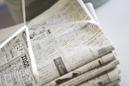 summarized: Bunch of newspaper that have been summarized in a plastic cord