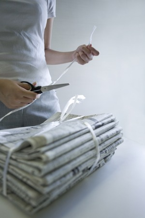 bundling: Woman to cut the plastic straps that surplus by bundling the newspaper with scissors