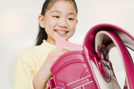 teaching material: Girl you are out of the textbook to school bag Stock Photo