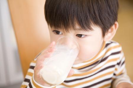 少年は牛乳を飲んでいます。 写真素材