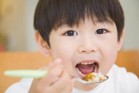 comiendo cereal: Muchacho que come el arroz al curry