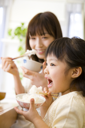 Mother and daughter to eat rice Stock Photo