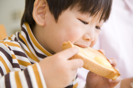 comiendo pan: El muchacho que está pegado a la tostada Foto de archivo