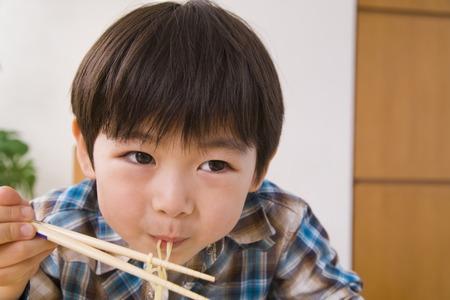 ラーメンを食べる少年