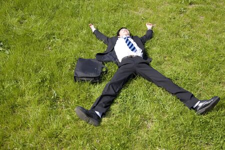 Businessman to lie down on the lawn