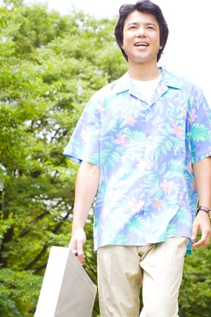short sleeved: Businessman of aloha shirt appearance to walk in the park Stock Photo