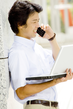 short sleeved: Businessman to talk on a mobile phone while holding a laptop