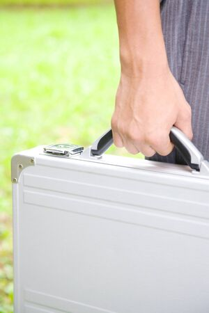 attache case: Hand of businessman with an attache case Stock Photo