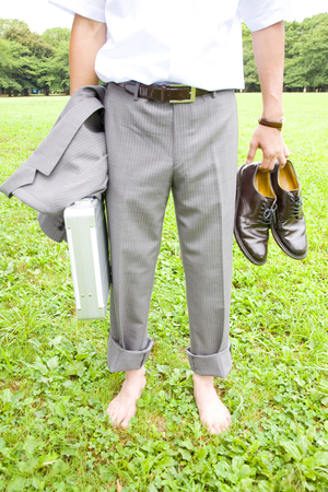 lower body: Lower body of businessman standing on the grass barefoot