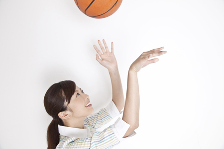 to toss: Women toss with both hands basketball