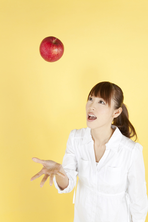 to toss: Women toss an apple on top Stock Photo