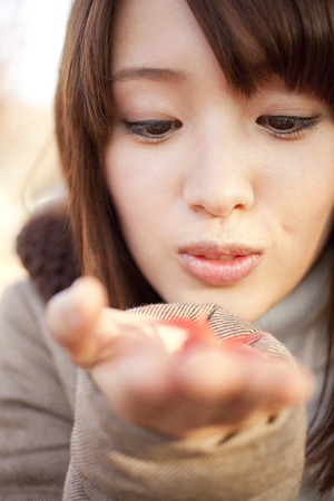 女性の笑顔があなたの手の手のひらにメープルをトッピング