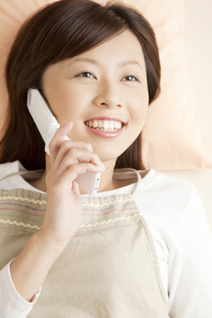 living beings: Women who phone lying down Stock Photo