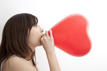 to inflate: Woman to inflate the heart-shaped balloons