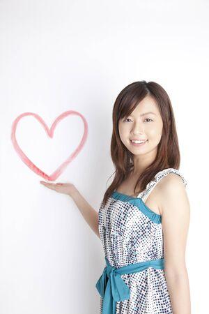 心臓を入れている女性はあなたの手の手のひらにマークします。