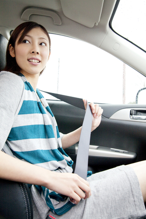 Women tighten the seat belt in the front passenger seat of the car