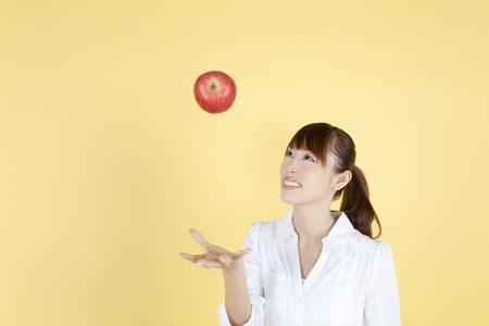 Women toss an apple on top Stock Photo