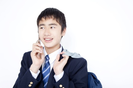 Mens junior high school students to talk on a mobile phone Stock Photo