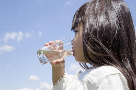 tomando agua: Muchacha que bebe un vaso de agua Foto de archivo