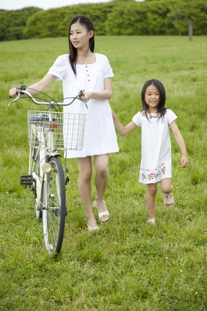 bicycle walk: Girls and young women by pressing the bicycle walk the prairie Stock Photo