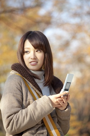 women face stare: Women who look back with a mobile phone Stock Photo