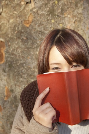 leaned: Women with a book leaned on a tree Stock Photo