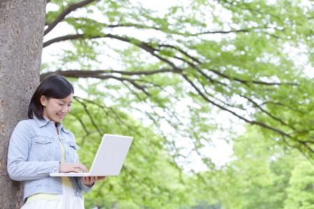 consuming: College students to operate the consuming laptop leaning on tree