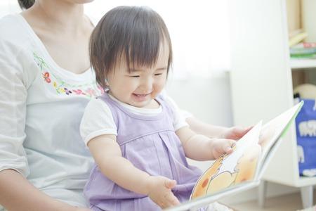 乳幼児: 女の子が母親に絵本を読んでもらう