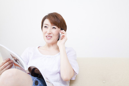 Middle women who phone while watching the magazine Stock Photo